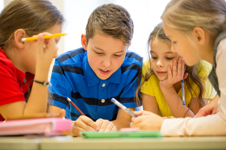 dětství: Skupina školní děti s pera a papíry psaní v učebně