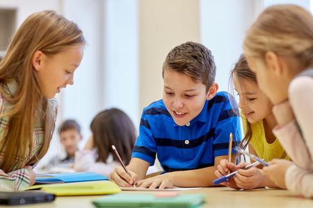 ni�os escribiendo: grupo de ni�os de la escuela con l�pices y papeles de escritura en el aula