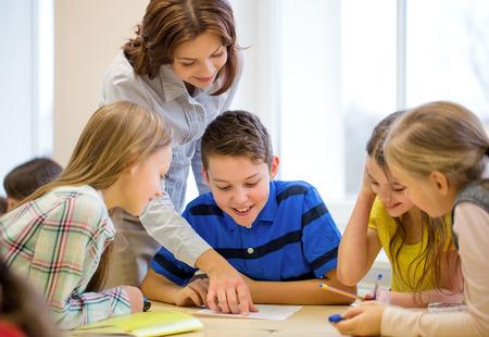 teacher helping school kids writing test in classroom