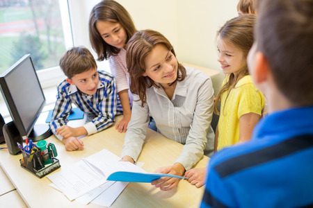 group of school kids with teacher talking in classroom Stock Photo