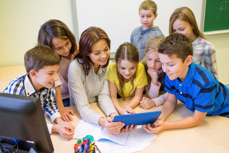 escuelas: grupo de niños de la escuela con el maestro mira al ordenador Tablet PC en el aula Foto de archivo