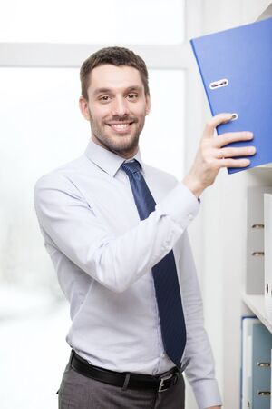 business and office concept - handsome businessman picking folder at office photo