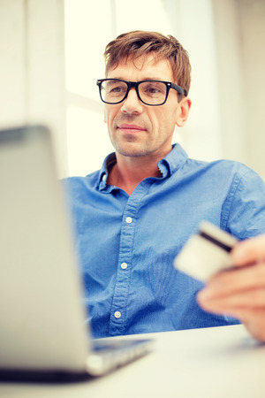 smiling man with laptop and credit card at home photo