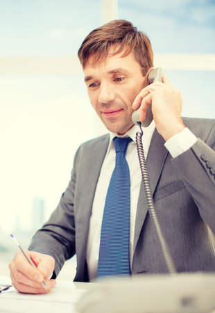 telephone salesman: technology, business, communication and office concept - handsome businessman working with phone and documents