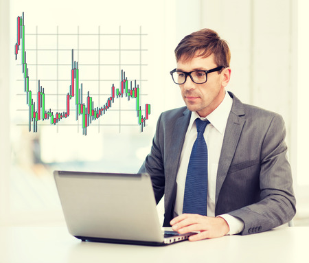 stock market chart: technology, money, business and office concept - handsome businessman in black eyeglasses with laptop computer and forex chart