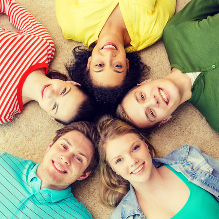 education and happiness concept - group of young smiling people lying down on floor in circle Stock Photo