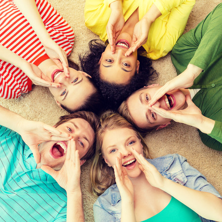 lying down on floor: education and happiness concept - group of young smiling people lying down on floor in circle screaming and shouting Stock Photo
