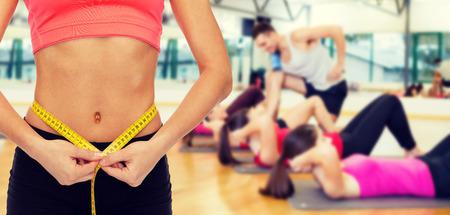 ダイエット、スポーツ、フィットネスおよびヒースのコンセプト - 測定テープでウエストを測定女性の手のクローズ アップ 写真素材