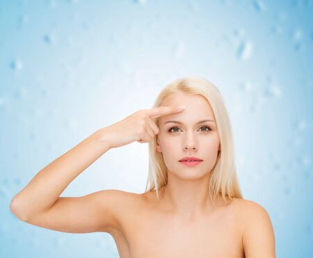 touching face: health and beauty concept - face of beautiful woman touching her forehead