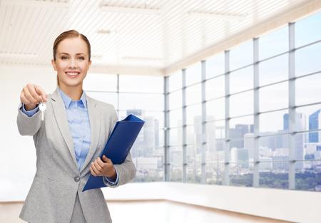 vendedor: negocios, bienes ra�ces, banca y la gente concepto - mujer de negocios sonriente con la carpeta y claves sobre sitio de la oficina o de fondo nuevo apartamento