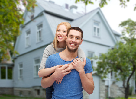 new homes:  smiling couple hugging over house background Stock Photo