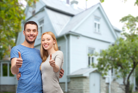 lachende paar knuffelen en tonen duimen omhoog over het huis achtergrond Stockfoto