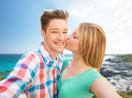 family love: happy couple taking selfie with smartphone or camera and kissing over sea shore background