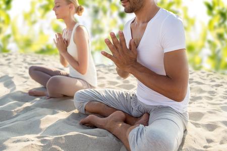 lachende paar maken van yoga oefeningen buiten zitten