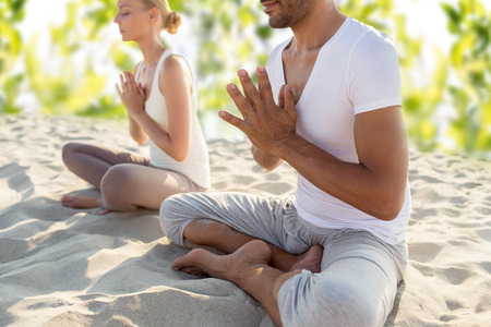 smiling couple making yoga exercises sitting outdoors