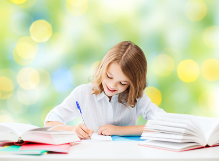 happy student girl sitting at table with books and writing in notebook over green lights background