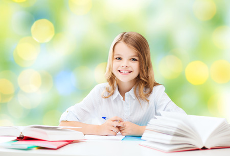 ni�os escribiendo: chica estudiante feliz sentado en la mesa con los libros y la escritura en el cuaderno sobre las luces de fondo verde