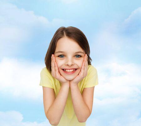 holding on head: smiling little girl holding head over white background