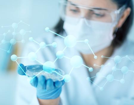 bata de laboratorio: la ciencia, la química, la biología, la medicina y la gente concepto - cerca de la mujer de ciencias joven con placa de Petri con polvo en laboratorio clínico