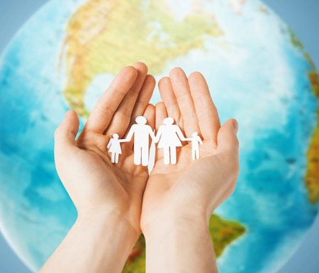 people, population, charity and life concept - close up of human hands holding paper family over earth globe and blue background Stockfoto