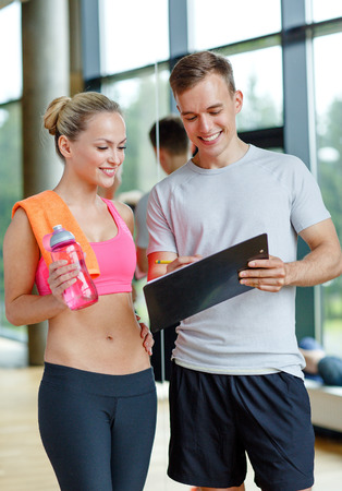 fitness, sport, exercising and diet concept - smiling young woman with personal trainer after training in gym Stock Photo