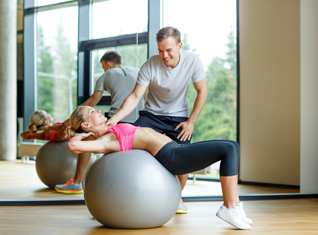six girl: fitness, sport, exercising and diet concept - smiling young woman and personal trainer in gym Stock Photo