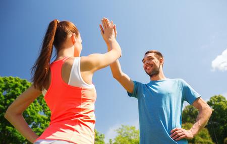 fitness, sport, opleiding en lifestyle-concept - twee lachende mensen die high five buiten