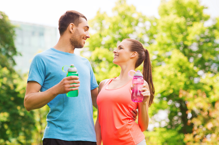 fitness, sport, friendship and lifestyle concept - smiling couple with bottles of water outdoors photo