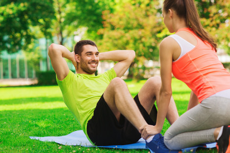 personal: fitness, sport, training, teamwork and lifestyle concept - smiling man with personal trainer doing exercises on mat outdoors