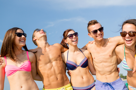 suntanned: friendship, sea, summer vacation, holidays and people concept - group of smiling friends wearing swimwear and sunglasses talking and laughing on beach
