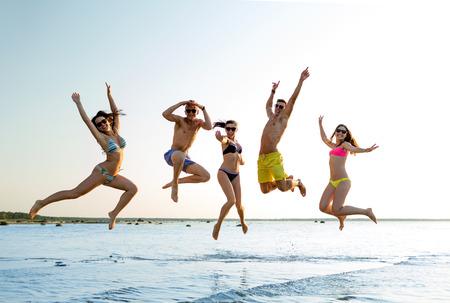 groep van lachende vrienden dragen van zwemkleding en een zonnebril springen op het strand