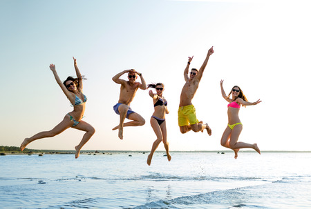 man jump:  group of smiling friends wearing swimwear and sunglasses jumping on beach Stock Photo