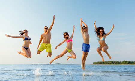 group of smiling friends wearing swimwear and sunglasses jumping on beach