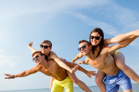 suntanned: group of smiling friends wearing swimwear and sunglasses having fun on beach Stock Photo