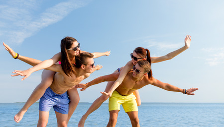 friendship, sea, summer vacation, holidays and people concept - group of smiling friends wearing swimwear and sunglasses having fun on beach photo