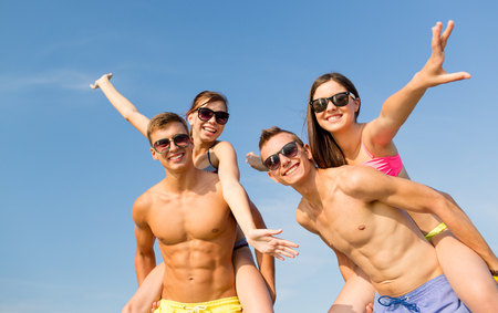 group of smiling friends wearing swimwear and sunglasses having fun on beach photo