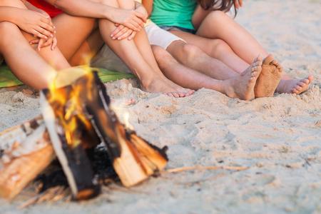 close up of friends sitting near fire on beach