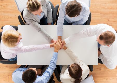 Unternehmen, Personen, Zusammenarbeit und Teamarbeit Konzept - Nahaufnahme von Kreativ-Team am Tisch sitzen und die Hände auf der jeweils anderen im Amt