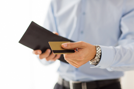 paying: people, business, finances and money concept - close up of businessman hands holding open holding wallet and credit card