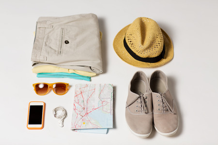 summer vacation, tourism and objects concept - close up of clothes, smartphone, personal stuff and travel map