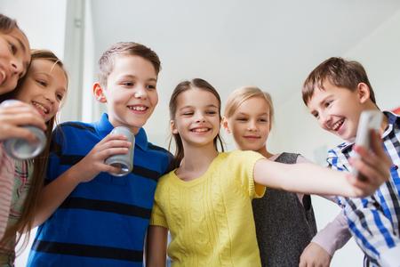 agua con gas: grupo de ni�os de la escuela con tel�fonos inteligentes y refrescos latas teniendo Autofoto en el pasillo