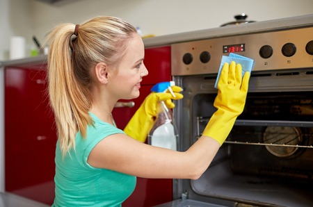 happy woman with bottle of spray cleanser cleaning oven at home kitchen Foto de archivo