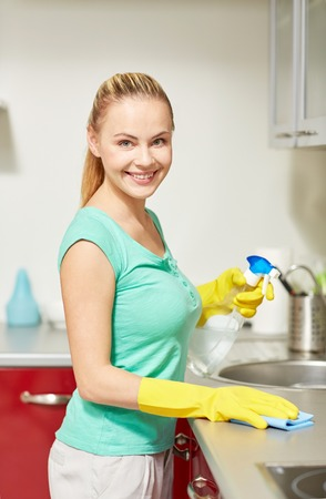 happy woman in protective gloves cleaning table with rag and cleanser at home kitchen Imagens