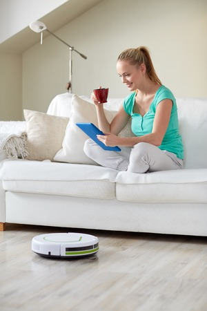 cleaner: people, housework and technology concept - happy woman with tablet pc computer and robot vacuum cleaner drinking tea at home Stock Photo