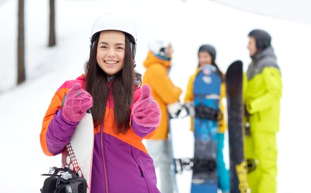 winter, leisure, extreme sport, friendship and people concept - happy young woman in helmet with snowboard and group of friends showing thumbs up photo