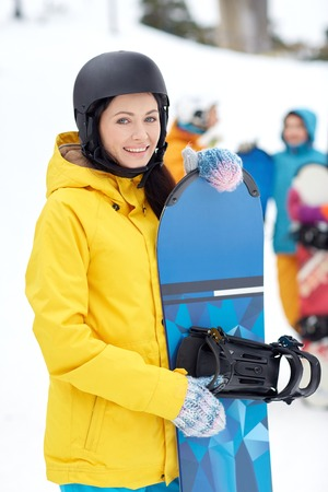 winter, leisure, extreme sport, friendship and people concept - happy young woman in helmet with snowboard and group of friends photo