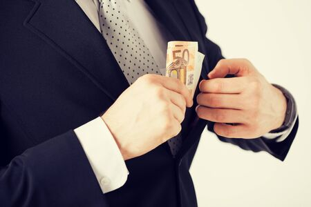hand in pocket: man hand putting euro cash money into suit pocket Stock Photo