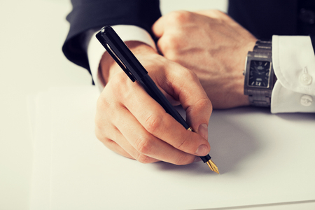 hand pen: picture of businessman writing something on the paper