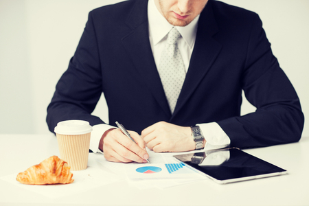 snack time: man with tablet pc and cup of coffee writing something Stock Photo