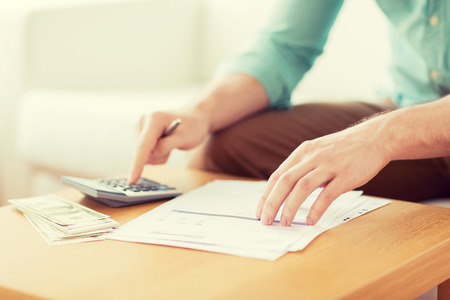 economies: savings, finances, economy and home concept - close up of man with calculator counting money and making notes at home
